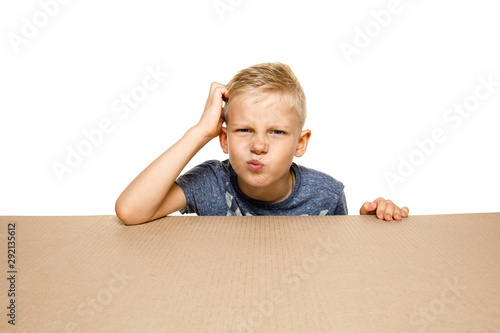 Fotografie, Obraz Cute and upset little boy opening the biggest postal package