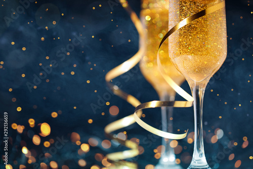 Fototapeta  Two glasses of champagne with golden confetti, glitter, serpentine and lights