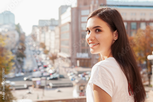 obraz dibond Gorgeous woman smiling to the camera over her shoulder, busy city streets on the background