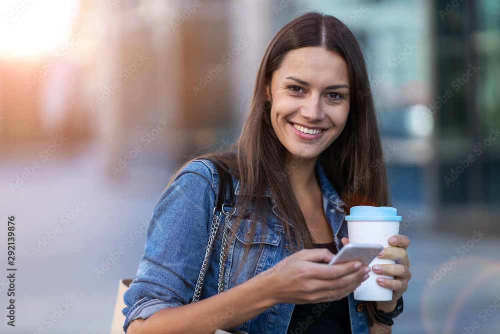 Fototapety, obrazy: Young woman with smartphone and coffee in the city