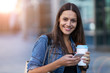 Leinwanddruck Bild - Young woman with smartphone and coffee in the city