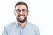 Leinwandbild Motiv Portrait of an authentic smiling young bearded brunette man with glasses on a white background