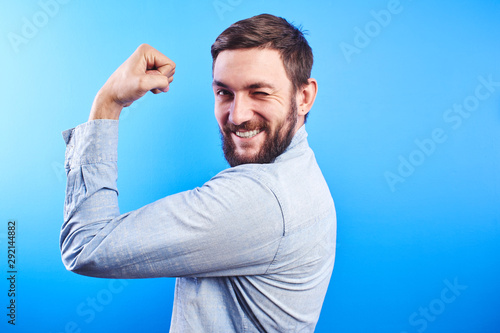 Vászonkép Young bearded confident man shows biceps demonstrating strength
