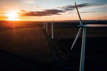 Aerial Of Wind Turbines At Sunrise In The English Countryside With A Dramatic Sky