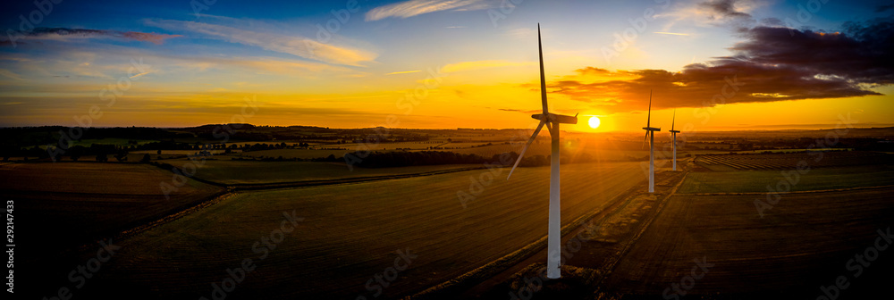 Fototapety, obrazy: Aerial of wind turbines at sunrise in the English countryside with a dramatic sky panoramic