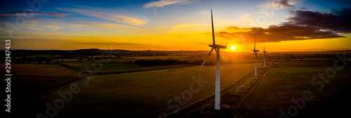 Obraz Aerial of wind turbines at sunrise in the English countryside with a dramatic sky panoramic - fototapety do salonu