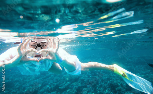 Deurstickers Ontspanning Happy girl in snorkeling mask dive underwater with tropical fishes in coral reef sea pool. Travel lifestyle, water sports, outdoor adventure, swimming lessons on family summer beach holiday with kids