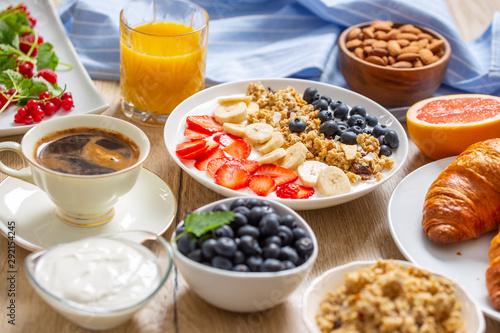Healthy breakfast served with plate of yogurt muesli blueberries strawberries and banana. - 292154245
