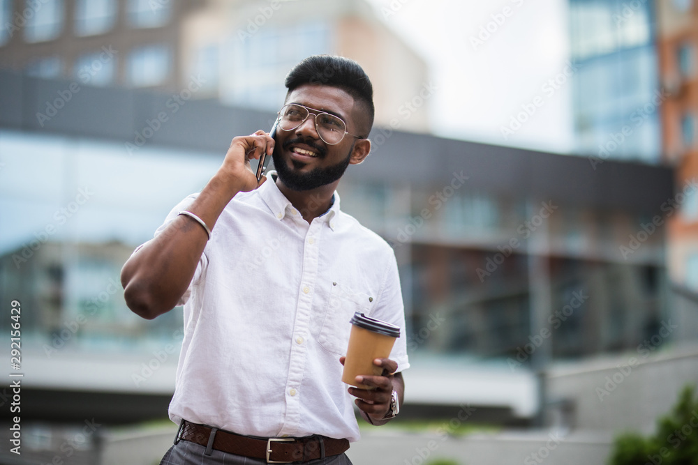 Fototapety, obrazy: Indian man talking on mobile phone and drinking coffee