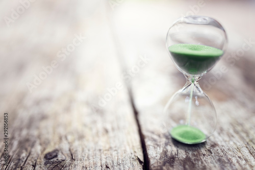 Obraz na plátně Green hourglass background concept for time or ecology and environmental conserv