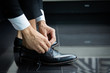 canvas print picture - Business man in a black suit tie a black leather shoe on black floor. The hands of a business man who is shoelace.