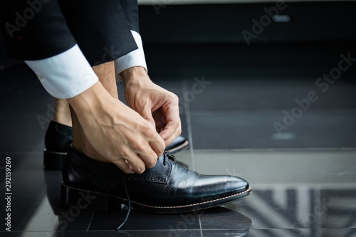 Obraz na plátně  Business man in a black suit tie a black leather shoe on black floor