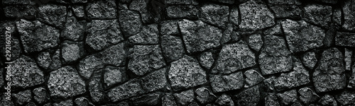 Photo sur Aluminium Cailloux Natural granite stone wall wide texture. Dark rock masonry widescreen gloomy gothic background