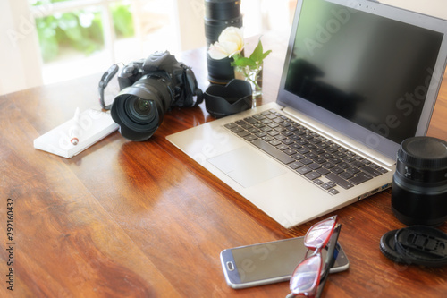 Fotomural  workplace of a female photographer with laptop, camera and lenses on a wooden ta