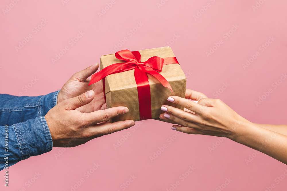 Fototapeta Top view of male and female hands holding red gift box with golden ribbon on pink background Flat lay. Present for birthday, valentine day, Christmas, New Year. Congratulations background copy space.