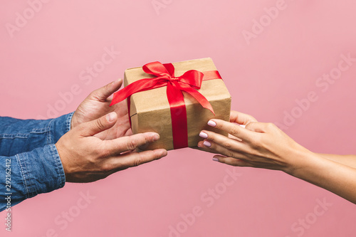 Fototapeta Top view of male and female hands holding red gift box with golden ribbon on pink background Flat lay. Present for birthday, valentine day, Christmas, New Year. Congratulations background copy space. obraz
