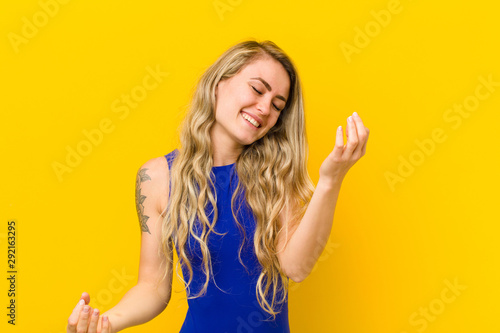 young blonde woman smiling, feeling carefree, relaxed and happy, dancing and listening to music, having fun at a party against yellow wall - 292163295