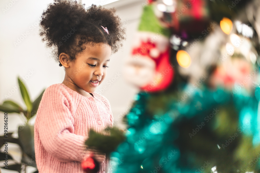 Fototapety, obrazy: Merry Christmas and Happy Holiday.Daughter decorate the Christmas tree . The morning before Xmas. .Happy little smiling girl .