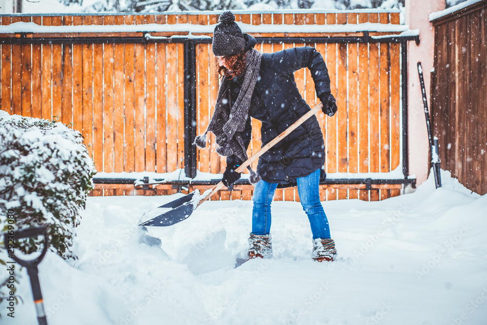 Fototapety, obrazy: woman with shovel cleaning snow. Winter shoveling. Removing snow after blizzard