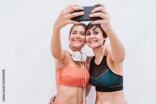 two friends women at the gym taking a selfie with mobile phone, smiling happily. Technology, sports and friendship concept - 292169618