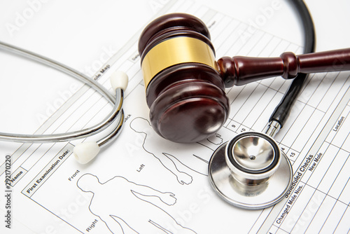 A wooden judge gavel and stethoscope on a medical chart Canvas Print