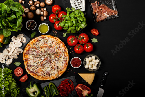 Poster Pizzeria Homemade pizza ready to eat with raw ingredients. Top view on a black background.