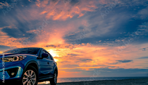 Tuinposter Nachtblauw Blue compact SUV car with sport and modern design parked by beach at sunset. Hybrid and electric car technology. Car parking space. Automotive industry. Car care business background. Beautiful sky.