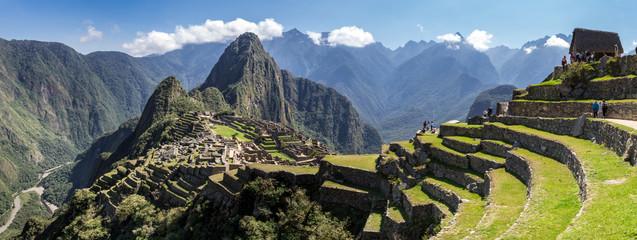 Panoramiczny widok na ruiny Machu Picchu w Peru. Za nami możemy podziwiać duże i piękne góry pełne zielonej roślinności. Stanowisko archeologiczne, światowe dziedzictwo UNESCO