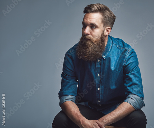 Fotografie, Obraz Young man sitting pensively against a gray background