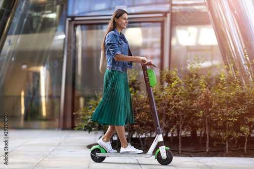 Fotografie, Obraz Carefree young woman riding an electric scooter
