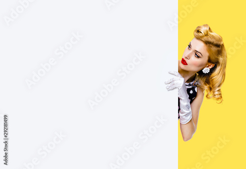 Fotografie, Obraz Portrait of beautiful blond girl in pin up style, showing blank signboard with c