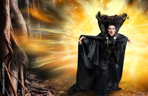Photo Scary witch conjuring a spell in the woods