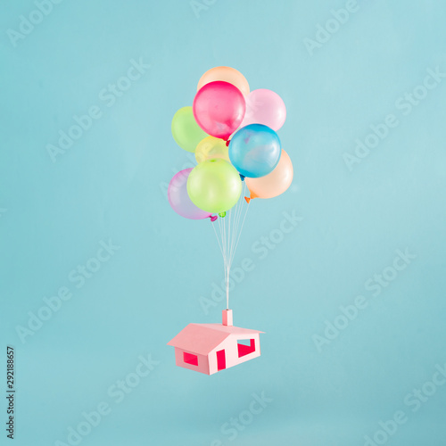 Fototapeta  Colorful balloons with pink house flies in the blue sky