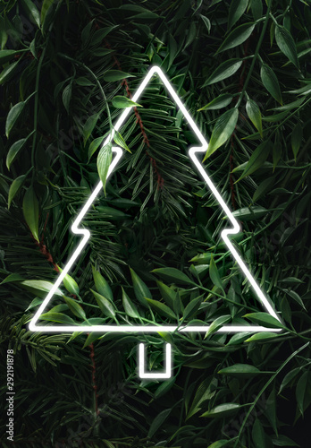 Creative fluorescent Christmas  layout made of leaves, branches and Christmas tree neon sign. Flat lay. Nature concept. - 292191878