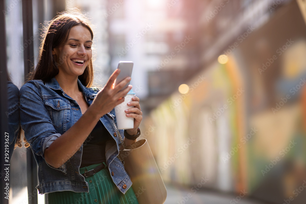 Fototapeta Young woman with smartphone in an urban city area