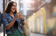 canvas print picture - Young woman with smartphone in an urban city area