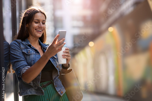 Fototapeta Young woman with smartphone in an urban city area obraz