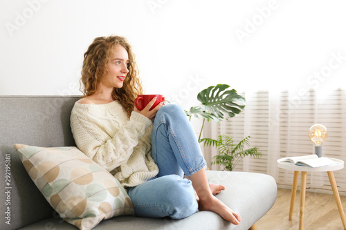 Young beautiful woman wearing white sweater on grey textile sofa at home Canvas Print