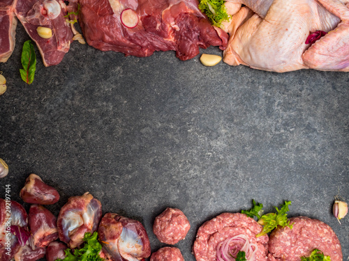 Fototapeta Assorted raw meat on dark background. Different types of meat and processed food. Top view, vintage toned image, blank space obraz