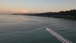Aerial birds eye view of a boat traveling on bay near Tacoma, Washington during sunset. Boat leaves wake behind it.