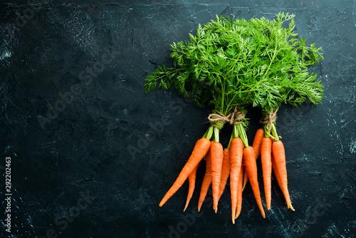 Obraz na plátně Fresh carrots on a black stone background