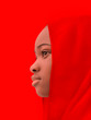 canvas print picture - Muslim girl wearing a red headscarf, twelve years old, profile view, red background