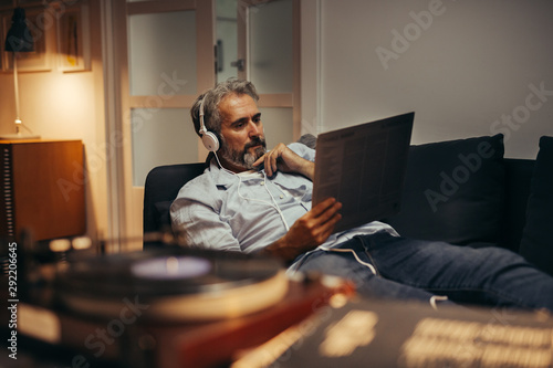 Fotografiet  mid aged man relaxed in sofa listening music on headphones in his home