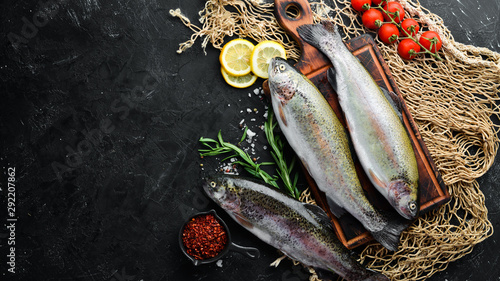 Fotografie, Obraz  Raw fish trout with vegetables on a black stone background