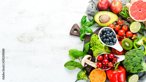 Fresh fruits and vegetables on a white wooden background. Top view. Free space for your text.