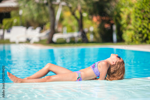Fototapeta Little adorable girl in outdoor swimming pool obraz na płótnie