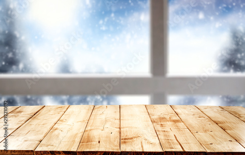 Wooden desk space and winter background of window and snow