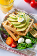 Belgian Waffles with avocado, eggs, micro green and tomatoes with orange juice on marble table. Perfect breakfast for healthy food or lose weight. Avocado sandwich.