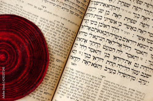 Fotografía An opened old Jewish Bible and red knitted jewish bale