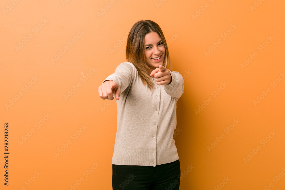 Fototapeta Young authentic charismatic real people woman against a wall cheerful smiles pointing to front.